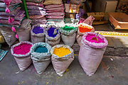 a stall selling paints and dyes at an Indian Market. Photographed in Ahmedabad, Gujarat, India