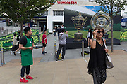 A Starbucks employee hands out the last free iced coffee to passers-by near a large hoarding showing the Mens and Ladies trophies, outside the Wimbledon railway station during the tennis championships, on 3rd July 2017, in Wimbledon, London, England.