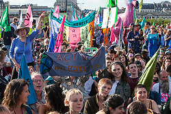 London, UK. 15 July, 2019. Climate activists from Extinction Rebellion pause for a water ceremony on Waterloo bridge during a march from the Royal Courts of Justice, where they had blocked the road for the day, to a camp site at Waterloo Millennium Green on the first day of the group's 'summer uprising', a series of events intended to apply pressure on local and central government to address the climate and biodiversity crisis.