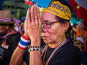 """15 NOVEMBER 2013 - BANGKOK, THAILAND: A Thai woman prays for Bhumibol Adulyadej, the King of Thailand, during an anti-government protest in Bangkok. Thai royalists accuse the government of Prime Minister Yingluck Shinawatra of not being supportive enough of the monarchy. Tens of thousands of Thais packed the area around Democracy Monument in the old part of Bangkok Friday night to protest against efforts by the ruling Pheu Thai party to pass an amnesty bill that could lead to the return of former Prime Minister Thaksin Shinawatra. Protest leader and former Deputy Prime Minister Suthep Thaugsuban announced an all-out drive to eradicate the """"Thaksin regime."""" The protest Friday was the biggest since the amnesty bill issue percolated back into the public consciousness. The anti-government protesters have vowed to continue their protests even though the Thai Senate voted down the bill, thus killing it for at least six months.     PHOTO BY JACK KURTZ"""