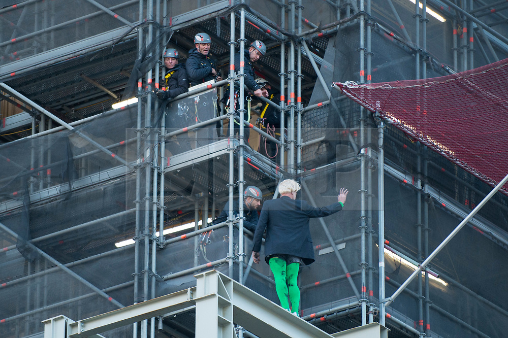 © Licensed to London News Pictures. 18/10/2019. LONDON, UK.  A climate activist from Extinction Rebellion waves to the public after scaling the construction scaffolding of the Queen Elizabeth Tower in Westminster.  Parliament Square and the surrounding area has been brought to a standstill as police and emergency services assess the situation.  Photo credit: Stephen Chung/LNP