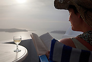Woman with a glass of wine, reading on a terrace balcony overlooking a bay in Imerovigli, balcony to the Aegean, an area in Fira village, Santorini, Greece