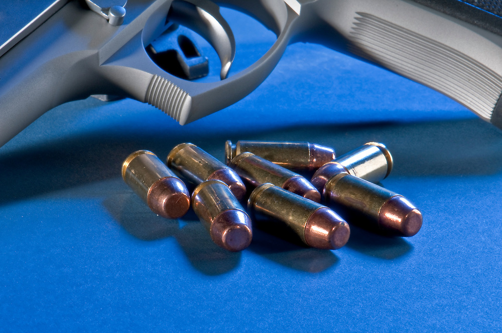 Close up view of bullets and gun. Use of selective focus.