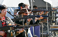 """This picture story:  Twice a year in a Kentucky """"holler"""" fans of automatic weapons gather for a """"machine gun shoot"""". Firing a wide variety of weapons from Uzi's to military .50 cal's they explode targets like junk cars and washing machines.....This picture: A variety of people with automatic weapons on the firing line at the Knob Creek Machine Gun Shoot near West Point, Kentucky April 9, 2005. Thousands of machine gun and military hardware enthusiasts attended the event held each year over weekends in the spring and fall."""