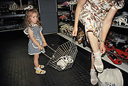 A young girl holds her mothers shopping basket while she tries on sandals in a department store in central Budapest, on 18th June 1990, in Budapest, Hungary.