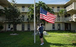 A man lowers the US flag in front of a condominium complex in preparation for the coming of hurricane Irma Friday, September 8, 2017 In Pompano Beach, FL, USA. Photo by /Paul Chiasson/CP/ABACAPRESS.COM