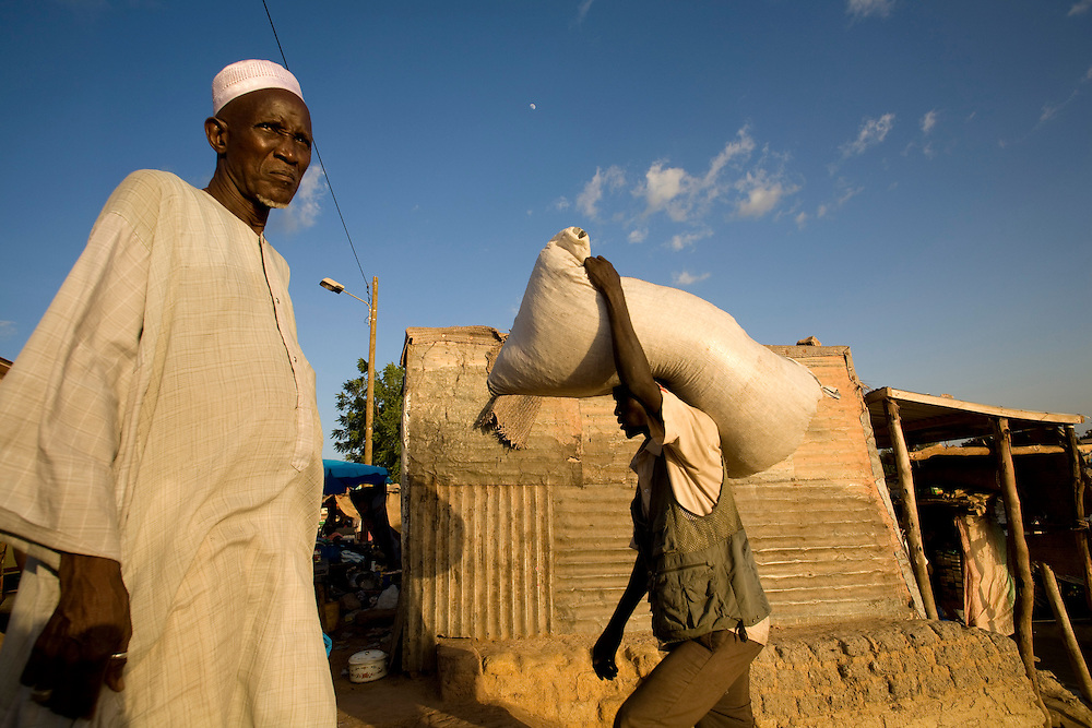 Men unloading  boat in Mopti's harbour. At the confluence of the Niger and the Bani rivers, between Timbuktu and Segou, Mopti is the second largest city in Mali, and the hub for commerce and tourism in this west-african landlocked country.
