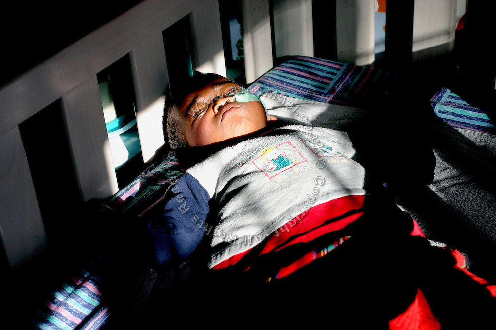 Masonwabe, 4, a HIV+ boy with cerebral palsy, is lying in his bed at Thembacare HIV+ children's care hospice in Athlone, Cape Town..