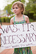A young girl holds a sign during a vigil outside the North Charleston City Hall during a rally following the shooting death of Walter Scott April 10, 2015 in Charleston, South Carolina. Scott was shot multiple times by police after running from a traffic stop.
