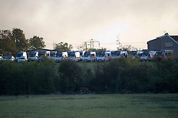 © Licensed to London News Pictures. 19/10/2011. Crays Hill, UK. A line of police riot vans near the Dale Farm site.  Residents at Dale Farm, the UK's largest illegal traveller site being evicted today (19/10/2011) following a long dispute with Basildon Council . Travellers and activist had barricaded themselves in to the site in an attempt to prevent their eviction. Photo credit: Ben Cawthra/LNP