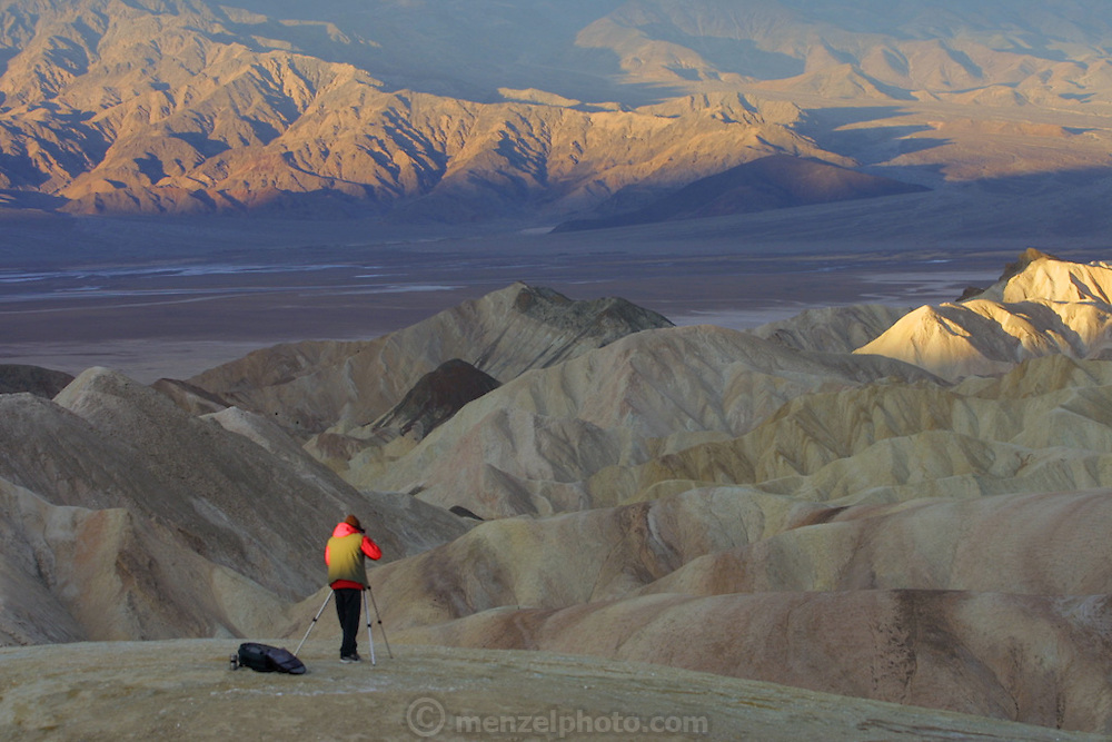 Death Valley, CA. A photographer shoots from Zabriskie Point at dawn with a tripod mounted camera.  Christmas road trip from Napa, California to Sedona, Arizona and back.