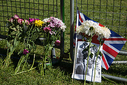 Windsor, UK. 17th April, 2021. Floral tributes, a Union Jack and a photograph are pictured alongside the Long Walk in Windsor Great Park on the day of the funeral of the Duke of Edinburgh. The funeral of Prince Philip, Queen Elizabeth II's husband, is taking place at St George's Chapel in Windsor Castle, with the ceremony restricted to 30 mourners in accordance with current coronavirus restrictions.