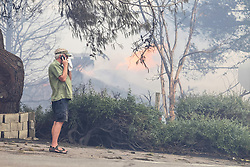 July 6, 2018 - Alpine, California, U.S. - FRED BEGLEY makes a phone call as his home burns in the background at the corner of Pine View Road and Olive View Road on Friday during a fire in Alpine amid a dangerous heat wave. A fast-moving brush fire in Alpine burned 400 acres, destroyed several structures and prompted evacuations. (Credit Image: © Eduardo Contreras/San Diego Union-Tribune via ZUMA Wire)