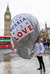 "© Licensed to London News Pictures. 08/03/2017. London, UK. A flashmob takes place in Parliament Square as part of International Women's Day.  Apparently backed by the Russian government, a giant balloon is unsuccessfully inflated bearing the text ""From Russia With Love"" and ""#makehersmile"" with organisers handing out roses to unsuspecting female passers by. Photo credit : Stephen Chung/LNP"