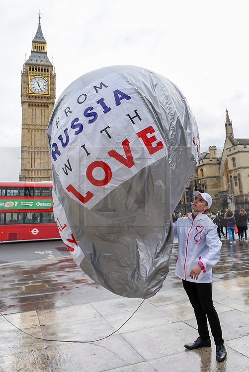 """© Licensed to London News Pictures. 08/03/2017. London, UK. A flashmob takes place in Parliament Square as part of International Women's Day.  Apparently backed by the Russian government, a giant balloon is unsuccessfully inflated bearing the text """"From Russia With Love"""" and """"#makehersmile"""" with organisers handing out roses to unsuspecting female passers by. Photo credit : Stephen Chung/LNP"""