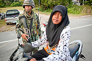 """Sept 26, 2009 -- PATTANI, THAILAND:  A Muslim woman passes a Thai soldier during a Thai army security operation near Krue Se Mosque in Pattani, Thailand, Sept. 26. Thailand's three southern most provinces; Yala, Pattani and Narathiwat are often called """"restive"""" and a decades long Muslim insurgency has gained traction recently. Nearly 4,000 people have been killed since 2004. The three southern provinces are under emergency control and there are more than 60,000 Thai military, police and paramilitary militia forces trying to keep the peace battling insurgents who favor car bombs and assassination.   Photo by Jack Kurtz / ZUMA Press"""