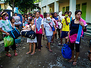 "22 JANUARY 2018 - CAMALIG, ALBAY, PHILIPPINES: Newly arrived evacuees from the eruption of the Mayon volcano walk into the Bariw National High School, the evacuation center they've been assigned to. There were a series of eruptions on the Mayon volcano near Legazpi Monday. The eruptions started Sunday night and continued through the day. At about midday the volcano sent a plume of ash and smoke towering over Camalig, the largest municipality near the volcano. The Philippine Institute of Volcanology and Seismology (PHIVOLCS) extended the six kilometer danger zone to eight kilometers and raised the alert level from three to four. This is the first time the alert level has been at four since 2009. A level four alert means a ""Hazardous Eruption is Imminent"" and there is ""intense unrest"" in the volcano. The Mayon volcano is the most active volcano in the Philippines. Sunday and Monday's eruptions caused ash falls in several communities but there were no known injuries.    PHOTO BY JACK KURTZ"