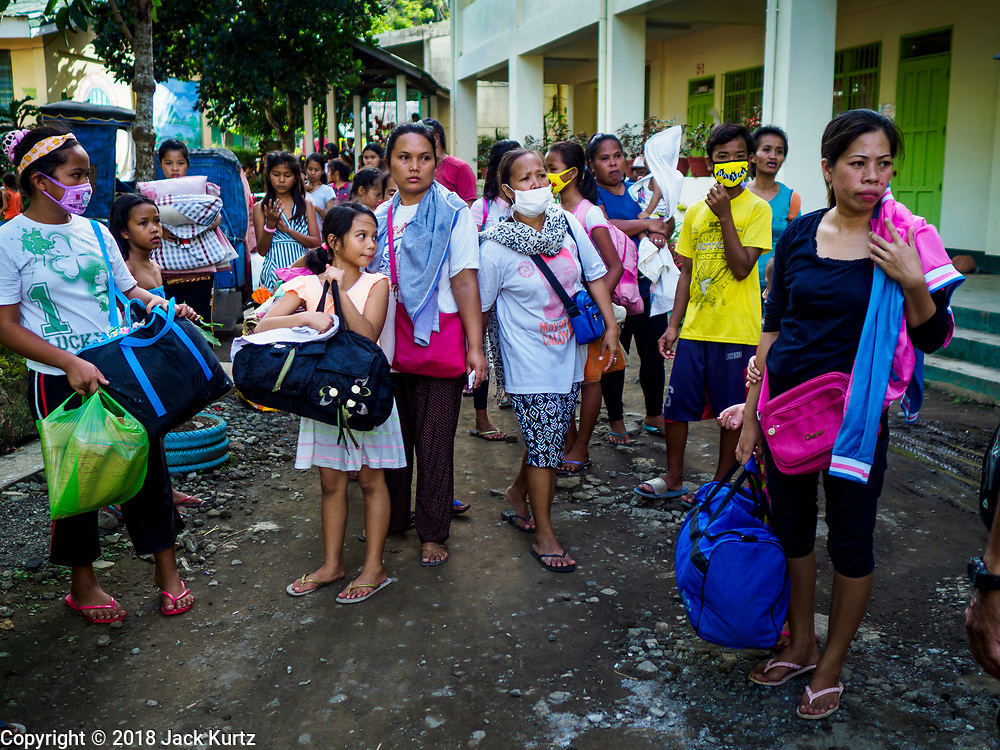 """22 JANUARY 2018 - CAMALIG, ALBAY, PHILIPPINES: Newly arrived evacuees from the eruption of the Mayon volcano walk into the Bariw National High School, the evacuation center they've been assigned to. There were a series of eruptions on the Mayon volcano near Legazpi Monday. The eruptions started Sunday night and continued through the day. At about midday the volcano sent a plume of ash and smoke towering over Camalig, the largest municipality near the volcano. The Philippine Institute of Volcanology and Seismology (PHIVOLCS) extended the six kilometer danger zone to eight kilometers and raised the alert level from three to four. This is the first time the alert level has been at four since 2009. A level four alert means a """"Hazardous Eruption is Imminent"""" and there is """"intense unrest"""" in the volcano. The Mayon volcano is the most active volcano in the Philippines. Sunday and Monday's eruptions caused ash falls in several communities but there were no known injuries.    PHOTO BY JACK KURTZ"""