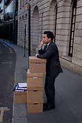 An office worker stands by a stack of office boxes on Fleet Street in the City of London. Waiting for colleagues and other employees to arrive, the man is in deep thought on this otherwise quiet sidestreet off Fleet Street in central London. The boxes may contain corporate or even legal paperwork as the law courts are nearby but important documents need safeguarding and the man is responsible for their security and confidentiality.