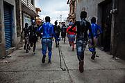 Un grupo de jóvenes con máscaras y pintados del cuerpo con aceite vegetal y pigmento corren por las calles durante el carnaval de San Nicolás de los Ranchos.