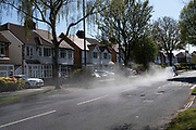 Car drives along a suburban street spewing exhaust fumes from its rear on 14th April 2020 in Birmingham, England, United Kingdom. The car, which must have a serious engine problem filled the air with air pollution smoke.