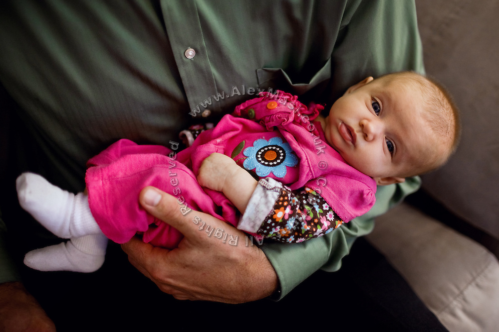 Benjamin Tippetts, 27, is holding his newborn daughter with his wife, inside their home in La Crosse, WI, USA, where he works as a freelance financial advisor. Benjamin has been an Army infantryman in Fallujah, fighting in the 2nd battle in 2004. ......