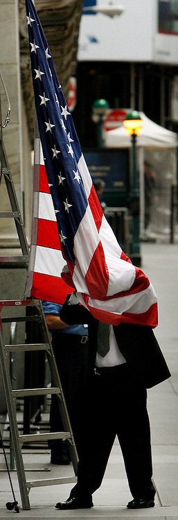 epa00733413 A man gets wrapped up in an American flag while taking it down at the end of the day outside the New York Stock Exchange in New York on Tuesday 06 June 2006. The Dow Jones Industrial average fell below 11,000 for the first time since March, partly due to Federal Reserve Chairman Ben Bernanke saying that the central bank will remain vigilant in fighting inflation.  EPA/JUSTIN LANE