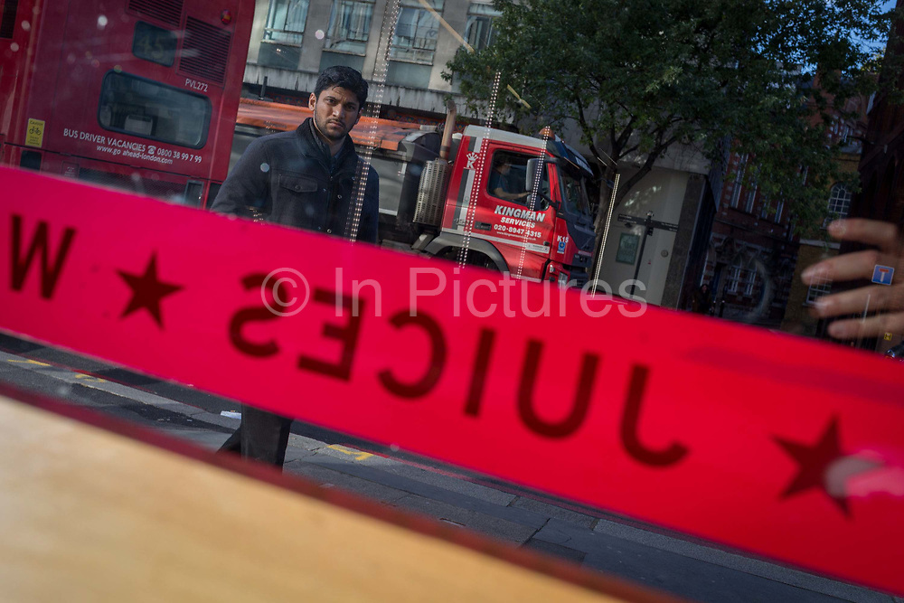 A man walks past a shop banner from the take-away food chain Pret a Manger which advertisises their Juices range in their window - a photo taken accidentally by the camera, on 27th October 2017, in London, England.