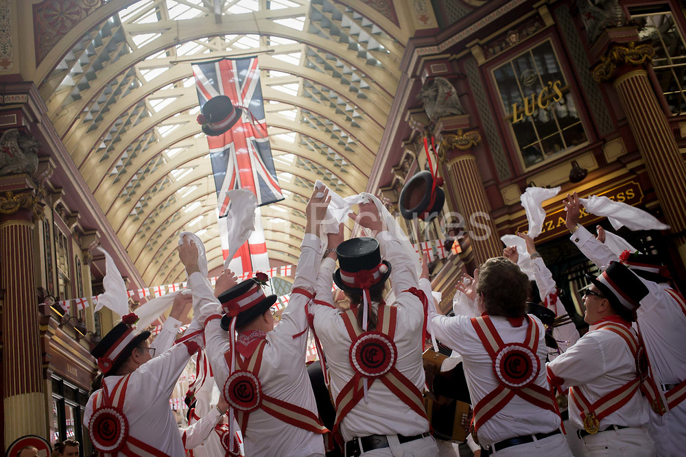 Morris man and lunchtime drinkers gather in Leadenhall Market on St George's Day (April 23rd), when 'Englishmen' celebrate their patron saint. Wearing white uniforms they jig their traditional dance, a form of English folk dance accompanied by accordion and pipes. It is based on rhythmic stepping and the execution of choreographed figures by a group of dancers. Implements such as sticks, swords, and handkerchiefs may also be wielded by the dancers. In a small number of dances for one or two men, steps are performed near and across a pair of clay tobacco pipes laid across each other on the floor. English records of Morris dancing date back to 1448.
