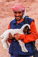 Bedouin man holding a baby lamb, Dana Biosphere Reserve, Wadi Feynan, Jordan.