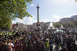 © Licensed to London News Pictures. 13/06/2020. London. BLM protesters gesture as they confront far-right group and British police officers at Trafalgar Square in central London, during a counter-protest against a Black Lives Matter demonstration, Saturday, June 13, 2020. British police have imposed strict restrictions on groups planning to protest in London Saturday in a bid to avoid violent clashes between protesters from the Black Lives Matter movement, as well as far-right groups. Photo credit: Marcin Nowak/LNP
