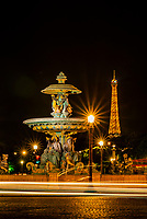 """One of the two monumental fountains at Place de la Concorde. This one is called """"Fountain of the RIvers."""" The illuminated Eiffel Tower is the background, Paris, France."""