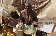 83 year old, Jok Tel, eats porridge, made of ocra and american donated sorghum, in the middle of a 110 F heat.  He arrived  to  Malakal together with 9 members of his family and hopes to get into their village of Maiwot after a long dusty trip from Khartoum.  (PHOTO: MIGUEL JUAREZ LUGO).