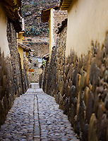 SACRED VALLEY, PERU - CIRCA SEPTEMBER 2019: Typical narrow cobblestone street in Ollantaytambo, a small village in the Cusco region known as Sacred Valley