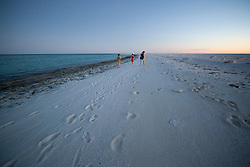 """Tourists from """"MV Odyssey"""", one of the Kimberley charter boats, walk on Bedwell Island at the Rowley Shoals.  Bedwell Island is a small sand cay, home to one of Western Australia's two only colonies of Red-tailed Tropicbirds (Phaeton rubricauda), and an important resting site for migratory birds."""