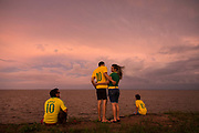 Immediately after the Confederations cup game between Brazil and Italy (4-2), fans celebrate the win by heading out into the streets. Seen here a group standing on the edge of the Amazon river on the line of the equator in Macapa city, Brazil.