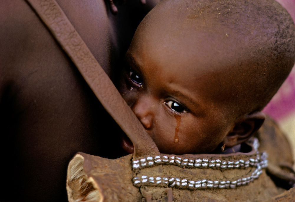 A malnourished infant, carried by her mother, struggles to survive in the unforgiving climate on the African plain.