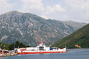 The narrow straight between Kamenari and Lepetani, view towards Perast and an impressive mountain top falling down to the sea bay Kotorski. The car and passenger ferry boat between Kamenari and Lepetani. Montenegro, Balkan, Europe.