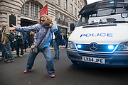 London, UK. Tuesday 11th June 2013. Protester dances to music beside a police van during demonstration against the upcoming G8 summit in central London, UK.