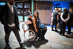 © Licensed to London News Pictures . 27/12/2015 . Wigan , UK . A wheelchair user gives a ride to a woman who has fallen on the pavement and cut her lip . Revellers in Wigan enjoy Boxing Day drinks and clubbing in Wigan Wallgate . In recent years a tradition has been established in which put on fancy dress for a Boxing Day night out . Photo credit : Joel Goodman/LNP