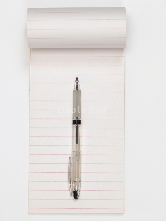 An open empty stenographers note book with a black pen.
