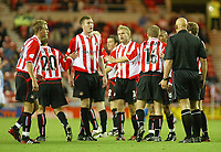 Photo. Andrew Unwin<br /> Sunderland v Huddersfield Town, Carling Cup Second Round, Stadium of Light, Sunderland 23/09/2003.<br /> Sunderland players argue with the referee, Mr M Cooper, after the goalmouth incident that saw Huddersfield Town's Andy Booth booked, Sunderland's Ben Clark sent off for handling the ball on the line and Huddersfield score their third goal.