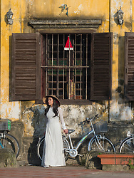 Asia, Vietnam, Hoi An, old town historic district.  UNESCO World Heritage Site. Woman in traditional Non La conical hat and white dress next to a bicycle. Editorial Use Only.