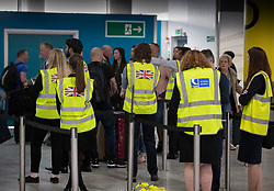 © Licensed to London News Pictures. 23/09/2019. Gatwick, UK. British Government officials wearing hi-vis vests walk stand ready to help at Thomas Cook check-in desks at Gatwick Airport after the travel firm collapsed overnight. The 178 year old travel operator has gone in to liquidation after rescue talks failed overnight. This will trigger the largest peacetime repatriation as more than 150,000 British holidaymakers will need to be brought home. Photo credit: Peter Macdiarmid/LNP