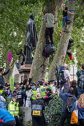 ©️ Licensed to London News Pictures. 02/09/2020. London, UK. Members of the Extinction Rebellion (XR) environmental campaign group climb trees at Parliament Square in central London to blockade Parliament. XR plan to peacefully disrupt the UK Parliament with actions planned over two weeks, until MP's back the Climate and Ecological Emergency Bill and prepare for crisis with a National Citizens' Assembly. Photo credit: Marcin Nowak/LNP
