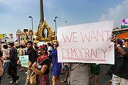 26 MAY 2014 - BANGKOK, THAILAND: People march past a portrait of Bhumibol Adulyadej, the King of Thailand, at Victory Monument during a pro-democracy rally in Bangkok. About two thousand people protested against the coup in Bangkok. It was the third straight day of large pro-democracy rallies in the Thai capital as the army continued to tighten its grip on Thai life.   PHOTO BY JACK KURTZ
