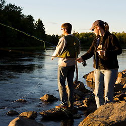 A couple fly-fishing on the Moose River below the dam on Brassua Lake in Rockwood, Maine.  Moosehead Lake region.