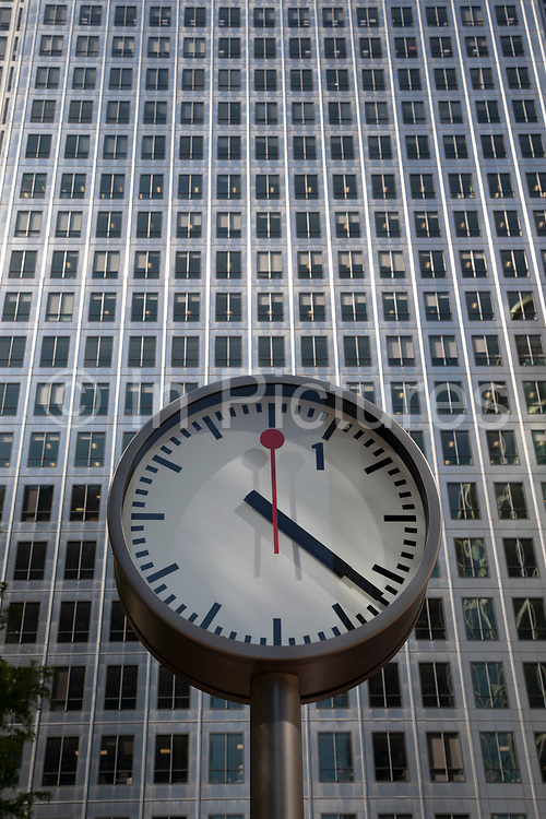 Clocks of Nash Court in Reuters Plaza at the base of One Canada Square in Canary Wharf financial district in London, England, United Kingdom. Canary Wharf is a financial area which is still growing as construction of new skyscrapers continues.