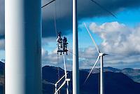 Workers hang from bucket to service blades of wind turbines in Kodiak, Alaska