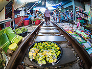27 SEPTEMBER 2016 - BANGKOK, THAILAND: A woman walks along the tracks, past a stand selling limes in the market in the train station in Samut Songkhram. The train from Baen Laem to Samut Songkhram (Mae Khlong) recently resumed service. The 33 kilometer track was closed for repair for almost a year. In Samut Songkhram, the train passes over the market. Vendors pull their stands out of the way and people step out of the way as the train passes through the market. It is one of the most famous train stations in Thailand and has become an important tourist attraction in the community.     PHOTO BY JACK KURTZ